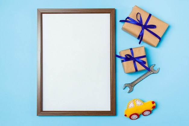 Vatertagskonzeptkarte mit dem arbeitswerkzeug des mannes auf den blauen hintergrund- und geschenkkästen eingewickelt im kraftpapier und mit blauem bogen gebunden. Premium Fotos