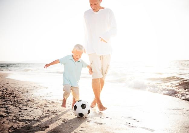 Vati und sohn, die fußball am strand spielen Kostenlose Fotos