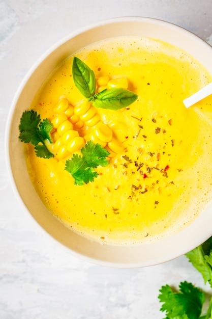 Vegane maissahnesuppe in weisser schale auf grauem untergrund, draufsicht, Premium Fotos