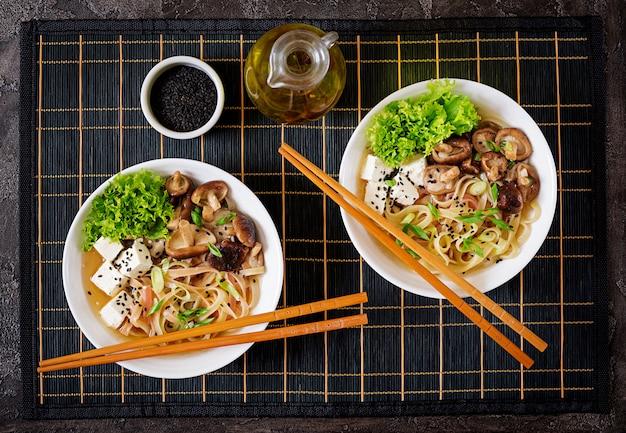 Vegane nudelsuppe mit tofu-käse, shiitake-pilzen und salat in weißer schüssel. Premium Fotos