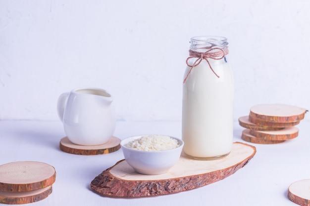 Vegane reismilch in einer glasflasche und reis in einer weißen platte auf einem holzständer auf einem weißen hintergrund Premium Fotos