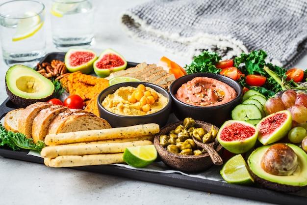 Vegane vorspeisenplatte, hummus, tofu, gemüse, obst und brot Premium Fotos