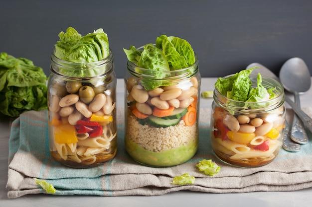 Veganer couscous- und nudelsalat in einmachgläsern mit gemüsebohnen Premium Fotos