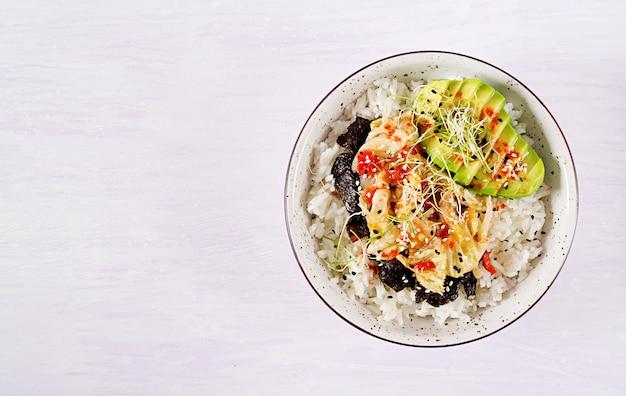 Veganer salat mit reis, eingelegtem kimchi-kohl, avocado, nori und sesam auf schüssel. Kostenlose Fotos