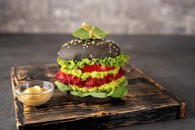 Veganer schwarzer burger mit avocado- und rübenpastetchen Premium Fotos