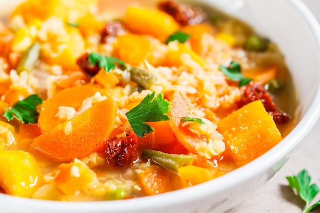 Vegetarische gemüsesuppe mit linsen und kürbis in der weißen platte. gesundes veganes lebensmittelkonzept. Premium Fotos