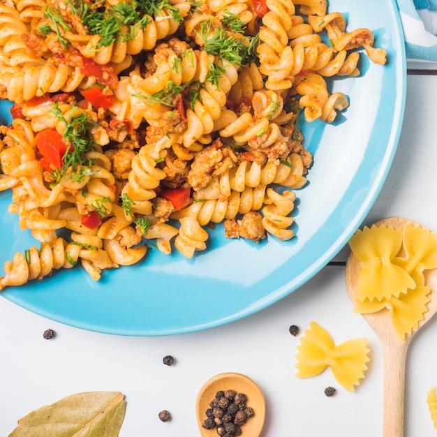 Vegetarische gemüseteigwaren fusilli auf blauer platte über weißem hintergrund Kostenlose Fotos