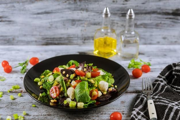 Vegetarische lebensmittelzutaten für salat mit mozzarella-, rucola- und kirschtomaten. Premium Fotos