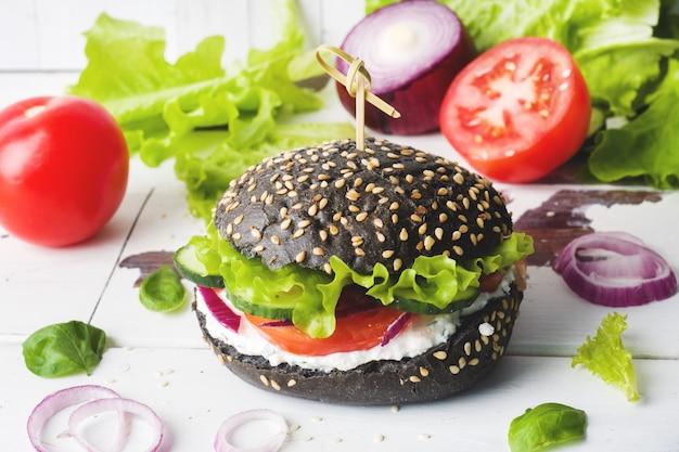 Vegetarischer burger mit hüttenkäsecreme und -gemüse. Premium Fotos