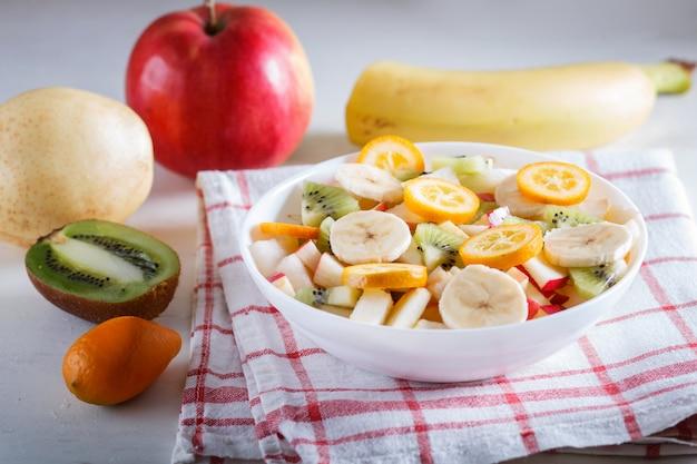 Vegetarischer salat aus bananen, äpfeln, birnen, kumquats und kiwi auf leinentischdecke Premium Fotos