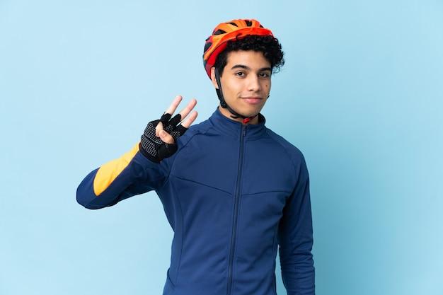 Venezolanischer radfahrermann lokalisiert auf blauem hintergrund glücklich und zählt drei mit den fingern Premium Fotos