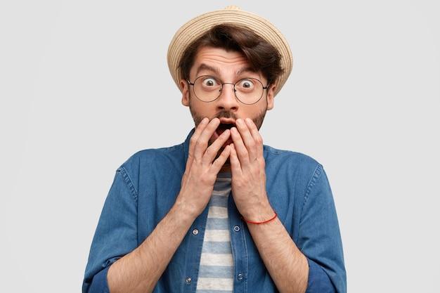 Verängstigter mann mit stoppeln, bedeckt den mund mit beiden händen, lässig gekleidet, kann seinen augen nicht glauben, sieht etwas überraschendes, isoliert über weißer wand Kostenlose Fotos
