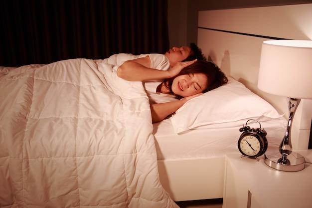 Verärgerte frau, die ihre ohren vom geräusch des ehemanns blockiert, der nachts schnarcht Premium Fotos