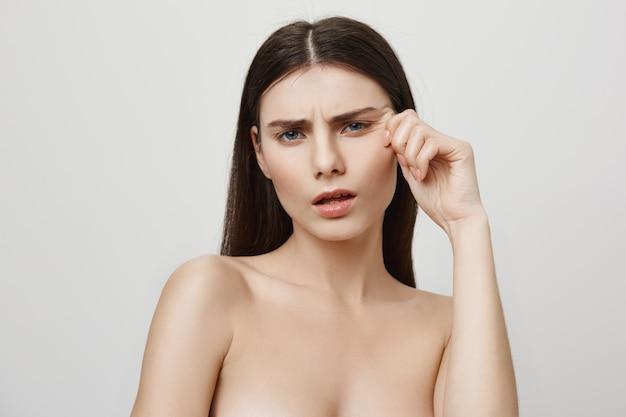 Verärgerte frau, die sich über gesichtsfalten, schönheits- und kosmetikkonzept beschwert Kostenlose Fotos