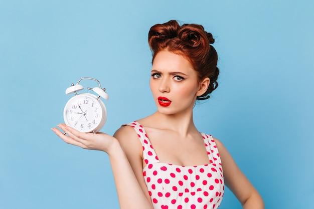 Verärgerte frau mit hellem make-up, das zeit zeigt. studioaufnahme des schönen pinup-mädchens mit uhr. Kostenlose Fotos