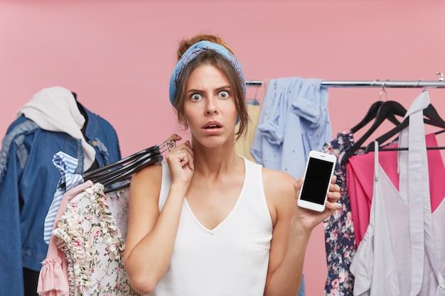 Verärgerte junge hübsche frau, die mit unzufriedenheit schaut, kleiderbügel mit kleidern auf der schulter hält, smartphone in der hand mit leerem bildschirm hält Kostenlose Fotos