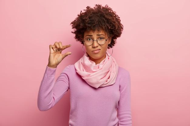 Verärgerte lockige frau formt kleine geste, zeigt etwas sehr winziges, trägt eine optische brille, einen lässigen pullover und einen schal Kostenlose Fotos