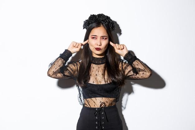 Verärgerte und belästigte asiatische stilvolle frau im halloween-kostüm, die sich über etwas lautes beschwert Kostenlose Fotos