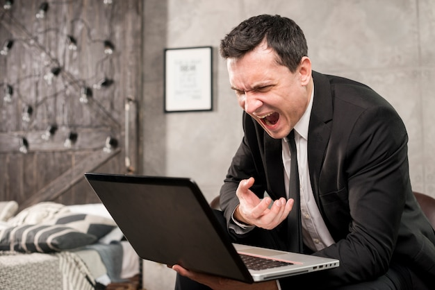 Verärgerter geschäftsmann, der zu hause am laptop kreischt Kostenlose Fotos