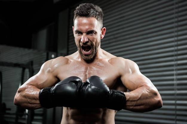 Verärgerter hemdloser mann mit boxhandschuhen schreiend an der crossfit turnhalle Premium Fotos