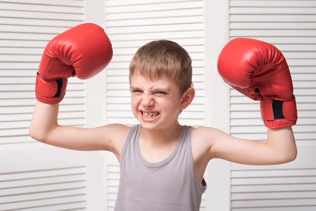 Verärgerter junge in den roten boxhandschuhen. Premium Fotos