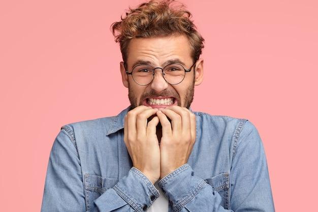 Verärgerter junger kaukasischer mann beißt die zähne zusammen und sieht mit missfallenem gesichtsausdruck aus, beißt fingernägel, sieht verzweifelt aus, fühlt abneigung, trägt jeanshemd, steht an der rosa wand. ach nein! Kostenlose Fotos
