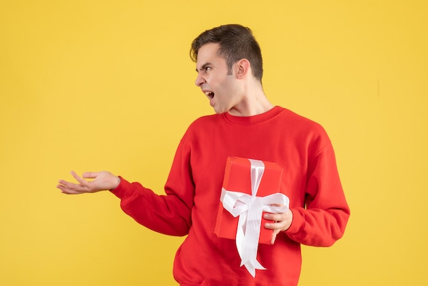Verärgerter junger mann der vorderansicht, der auf gelb steht Kostenlose Fotos