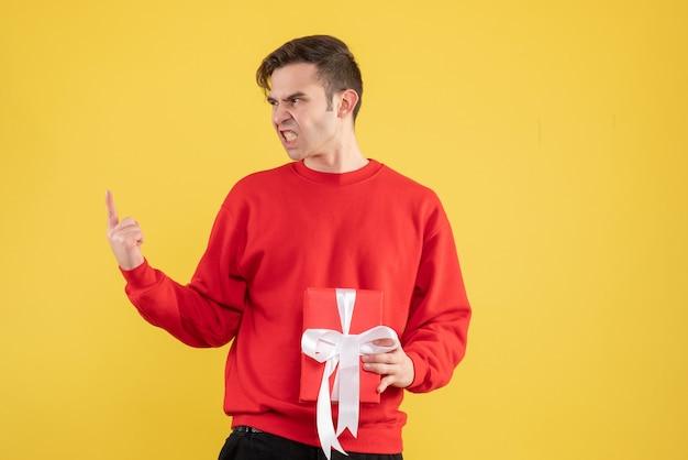 Verärgerter junger mann der vorderansicht mit dem roten pullover, der auf gelb steht Kostenlose Fotos