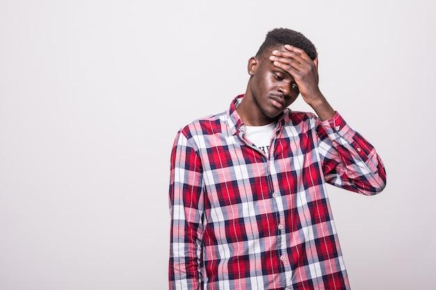 Verärgerter unglücklicher afroamerikanischer mann, der kopf mit händen drückt, sich vor schmerz krümmt, unter kopfschmerzen leidet. menschen, stress, anspannung und migräne Kostenlose Fotos