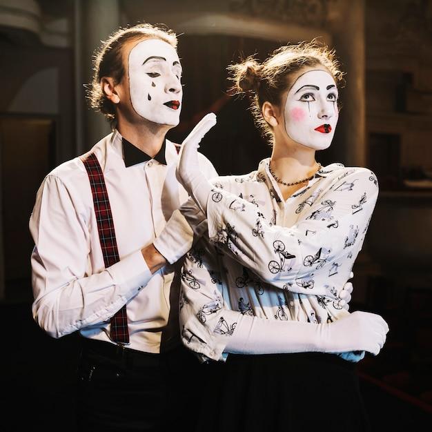 Verärgerter weiblicher pantomimen, der dem männlichen pantomimen, der hinter ihm steht, kein handzeichen zeigt Kostenlose Fotos