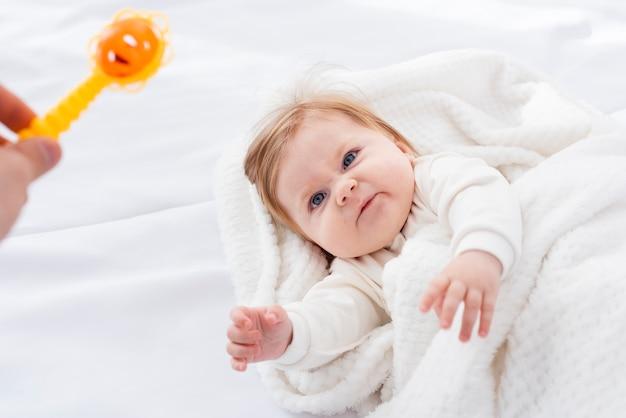 Verärgertes baby in der decke, die spielzeug wünscht Kostenlose Fotos