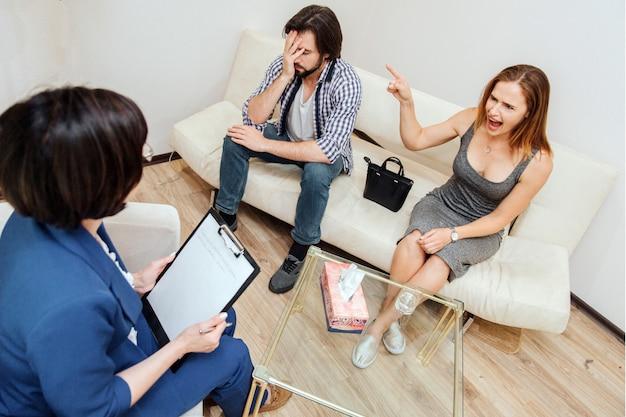 Verärgertes mädchen sitzt auf sofa mit ihrem ehemann. sie schaut auf die therapeutin, schreit aber und zeigt auf den mann. Premium Fotos