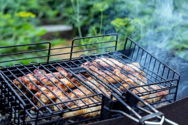 Verarbeiten sie das kochen von fleischigem steak auf einem grill im freien. picknick, essen im freien. metallgrill Premium Fotos
