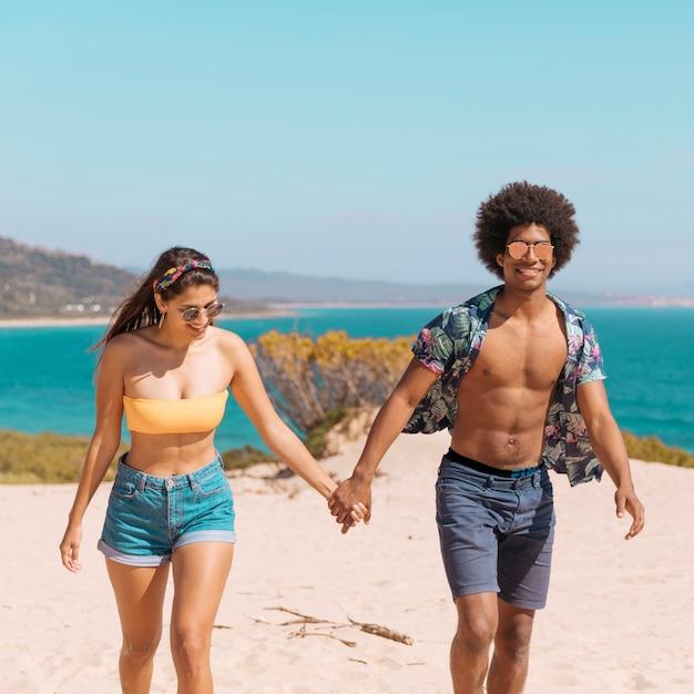 Verbinden sie das händchenhalten, das auf dem strand steht, der kamera lächelt und betrachtet Kostenlose Fotos