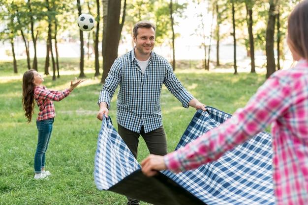 Verbinden sie das platzieren der decke auf gras nahe ihrer tochter, die fußball im garten spielt Kostenlose Fotos