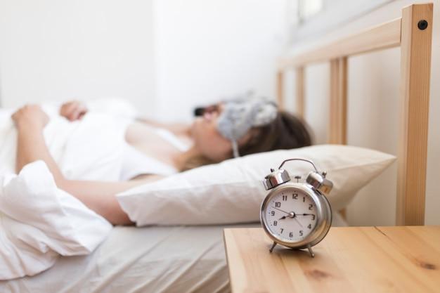 Verbinden sie das schlafen auf bett mit wecker über hölzernem schreibtisch Kostenlose Fotos
