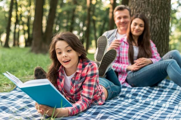 Verbinden sie das sitzen hinter ihrem netten mädchen, das auf umfassendem lesebuch im park liegt Kostenlose Fotos