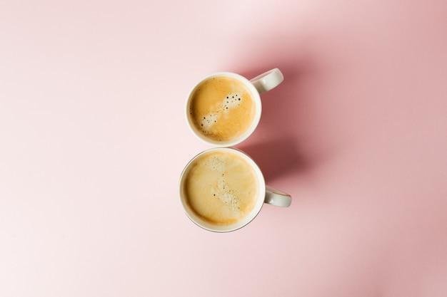 Verbinden sie weiße schalen mit kaffee auf rosa pastellhintergrund, minimales konzept der feier am 8. märz Premium Fotos