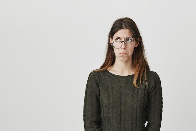 Verblüffte und verwirrte junge frau in krummen gläsern, die beunruhigt nach links schaut Kostenlose Fotos