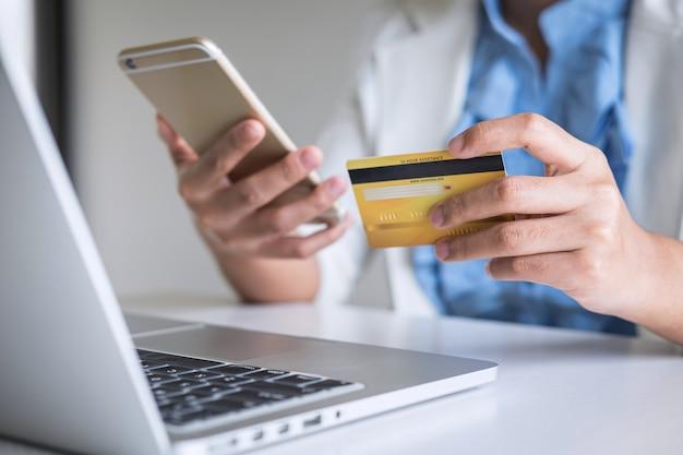 Verbraucher der jungen frau, der smartphone, kreditkarte hält und auf laptop für das on-line-einkaufen und die zahlung schreibt, schließen einen kauf im internet, eine on-line-zahlung, eine vernetzung ab und kaufen produkttechnologie Premium Fotos