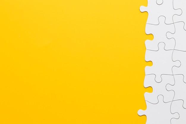 Verbundenes puzzlestück auf gelbem hintergrund Kostenlose Fotos
