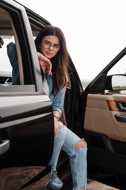Verführerische frau mit brille, die alleine mit dem auto fährt Kostenlose Fotos