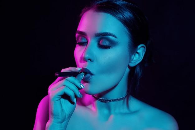 Verführerische herrliche brunettefrau des zaubers, die elektronische zigarette raucht Premium Fotos