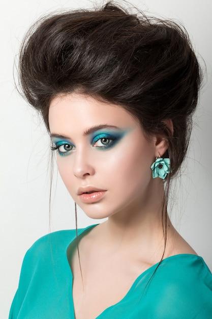 Verführerische junge brünette frau in einem türkisfarbenen kleid, das ohrring trägt Premium Fotos