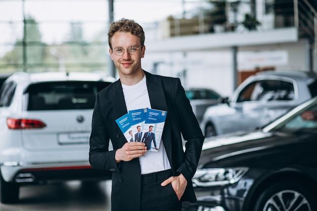 Verkäufer an einem autosalon mit geschäftsflugblättern Kostenlose Fotos