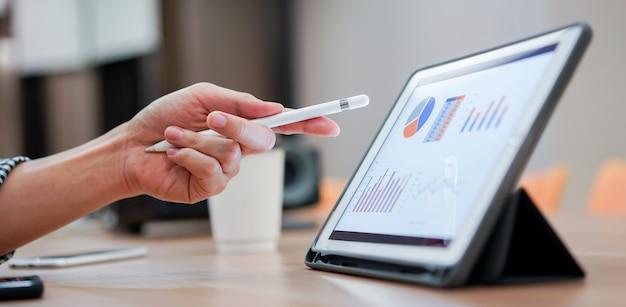 Verkäufer, der stift zum zeigen auf tablettenschirm verwendet, um firmengewinn im sitzungsereignis zu zeigen Premium Fotos