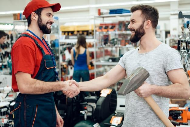 Verkäufer gibt bärtigem kunden neuen riesigen hammer. Premium Fotos
