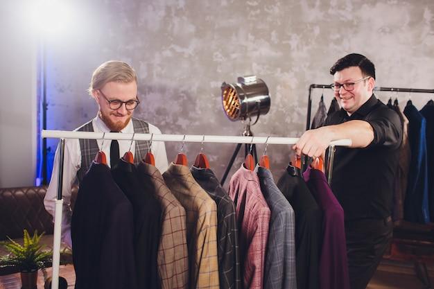 Verkäufer hilft mann bei der auswahl einer jacke Premium Fotos