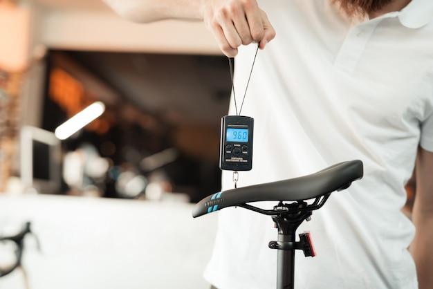 Verkäufer im fahrradladen wiegt eines der fahrräder. Premium Fotos