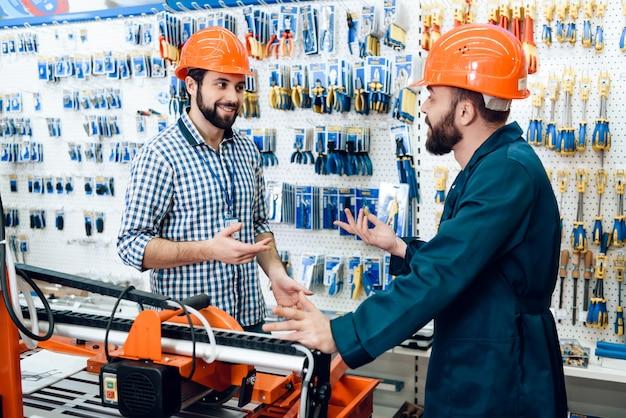 Verkäufer in bauhelmen diskutieren ausrüstung. Premium Fotos